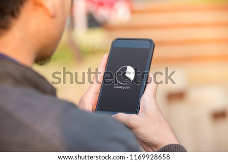 Installing application process on smartphone concept. Man holding smartphone doing installing update. #1169928658