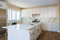 Installing cabinets and counter top in a white kitchen partially installed furniture.