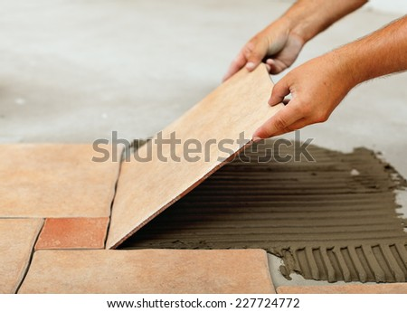 Installing ceramic floor tiles - placing the tile into the adhesive material bedding, closeup