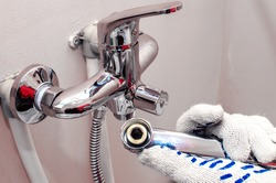 Installing faucet. Plumber fixing water tap. Men's hands in gloves are fixing bath tap into place.