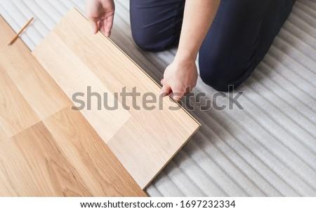 Installing laminated floor, detail on man hands fitting wooden tile, over white foam base layer Stok fotoğraf ©