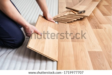 Installing laminated floor, detail on man hands holding wooden tile, over white foam base layer, small pile with more tiles background Zdjęcia stock ©