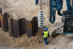 installing sheet piling on construction site with drilling rig