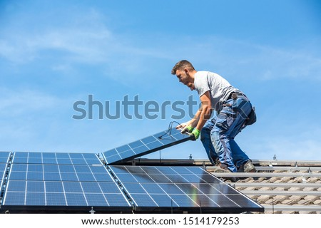 Installing solar photovoltaic panel system. Solar panel technician installing solar panels on roof. Alternative energy ecological concept. Photo stock ©