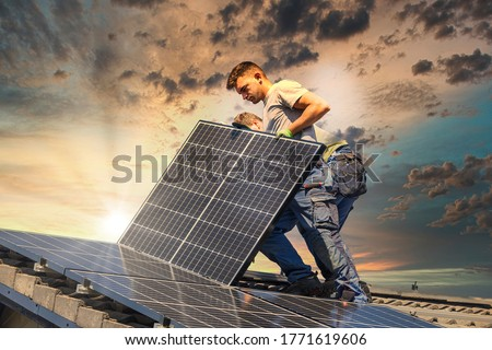 Installing solar photovoltaic panel system. Solar panel technician installing solar panels on roof. Alternative energy ecological concept. Foto stock ©