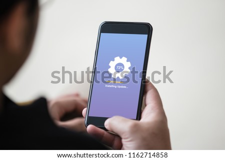 Installing update concept on phone screen. Man hand holding phone doing installing update process with gearbox percentage progress and loading bar. #1162714858