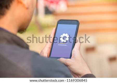Installing update concept on phone screen. Man holding phone doing installing update process with gearbox percentage progress and loading bar. #1169306845
