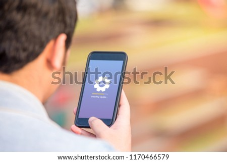 Installing update concept on phone screen. Man holding phone doing installing update process with gearbox percentage progress and loading bar. #1170466579