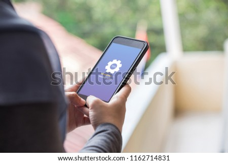 Installing update concept on phone screen. Woman hand hold phone doing installing update process with gearbox percentage progress and loading bar. #1162714831