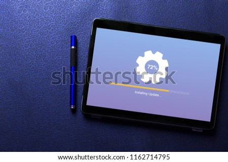 Installing update process with gearbox percentage progress and loading bar concept on tablet screen with blue pen on blue pattern textured background #1162714795