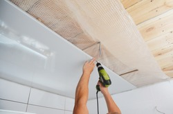 Installing wall and ceiling panels on planked wood ceiling covered with vapor barrier membrane using screwdriver while bathroom renovation, remodel.