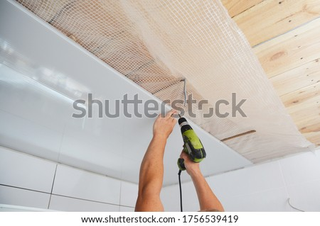 Photo of  Installing wall and ceiling panels on planked wood ceiling covered with vapor barrier membrane using screwdriver while bathroom renovation, remodel.
