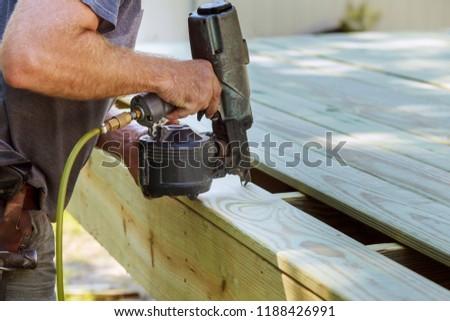 Installing Wood on deck, patio construction man using pneumatic gun