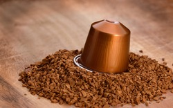 instant coffee granules and capsule on a wooden tray