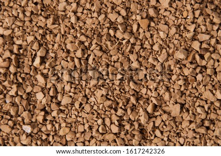 Instant coffee granules close-up, brown background with place for text