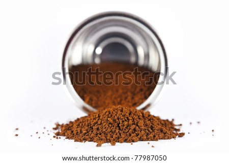 Instant coffee poured from a metal tin on a white background.