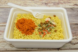Instant dryed noodles with dry vegetables, spices with red pepper in disposable container with plastic fork. Traditional cheap Asian food. Fast food, raw noodles. Selective focus, blurred background