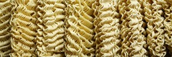 Instant noodles.Close up of raw dried noodles.Uncooked noodles texture.Precooked dehydratenoodleblocks.Asian food. Food background.Full depth of field. Panoramic image. Hi-res banner.