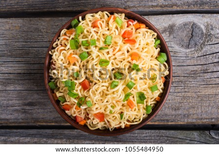Instant noodles in bowl with carrot , tomatoes and onion
