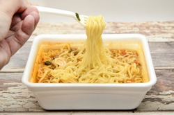 Instant noodles with dry vegetables and spices with red pepper in disposable container with plastic fork. Traditional cheap Asian food. Fast food, most popular. Selective focus, blurred background