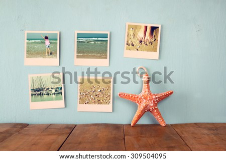 instant photos hang over wooden textured background next to decorative starfish. retro filtered image