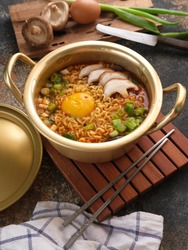 Instant Ramyun or Korean Spicy Noodle Soup with mushroom, egg and spring onion served on Yellow Aluminum stockpot - Korean Food Traditional Style
