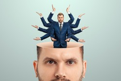 Instead of a brain, a man has a multi-armed businessman in his head. Creative picture, concept of multitasking, multi-hands, brain work, stress resistance
