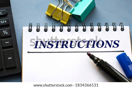 INSTRUCTIONS word is written in a notebook with a marker, calculator, clamps and cactus. Business concept Stock photo ©