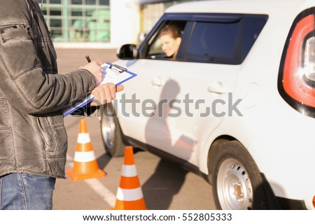 Instructor in driving school writing down results of exam #552805333