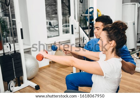 Instructor in the gym helps a woman perform exercises. Exercises with dumbbells to strengthen muscles of hands