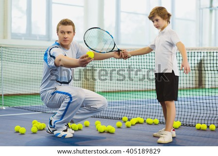 Instructor or coach teaching child how to play tennis on a court indoor