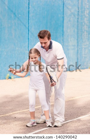 Instructor teaching a child how to play tennis on a court outdoor