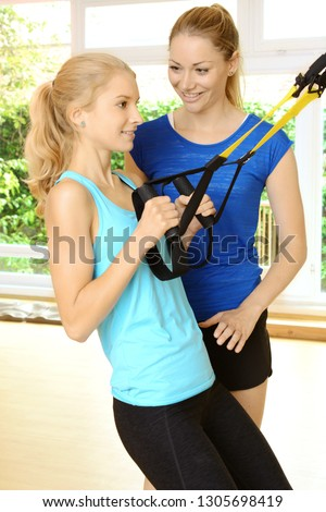 Instructor with girl excercising with sling trainer or suspension trainer in gym