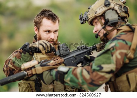 Instructor with soldier aiming rifle at firing range