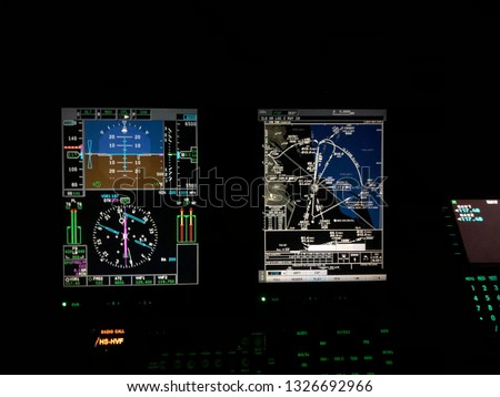 Instruments panel of a helicopter cockpit flying over the airfield or airport at night. Interior of helicopter control dashboard at night with glass cockpit or fly-by-wire system. a complex aircraft.