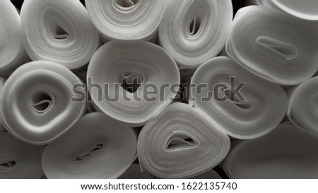 Insulating roll.Many insulating rolls of expanded polystyrene.Material for sound insulation or simply insulation in a house, apartment or room. Plastic.Rolls in a warehouse of goods. Closeup.
