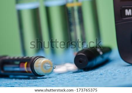 Insulin pen, vials and pills on blue surface
