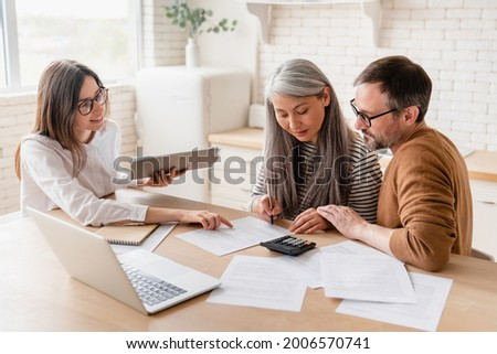 Insurance agent consulting mature family couple, discussing health insurance, signing contract deal of loan pension mortgage at home, calculating funds, investments, savings