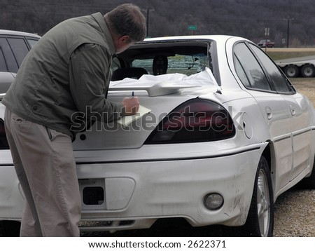 Insurance agent looks at vehicle for claim resolution
