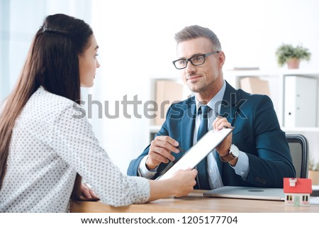 insurance agent pointing at clipboard in clients hand at tabletop in office, house insurance concept