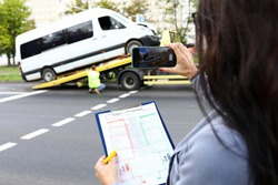 Insurance agent records accident on his phone and evaluates car. Car accident concept