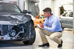 Insurance assessor making notes on a clipboard while inspecting a damaged vehicle at a garage.