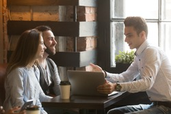 Insurance broker or salesman making offer to young millennial couple using laptop in cafe, realtor consulting customers about mortgage sitting at coffeehouse table pointing on computer screen