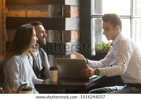 Insurance broker or salesman making offer to young millennial couple using laptop in cafe, realtor consulting customers about mortgage sitting at coffeehouse table pointing on computer screen #1016244037