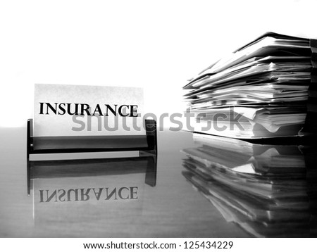 Insurance card on desk with files