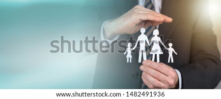 Insurance concept, man protecting a family with his hand; panoramic banner