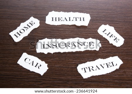 Insurance concept.Torn paper with different types of insurance
