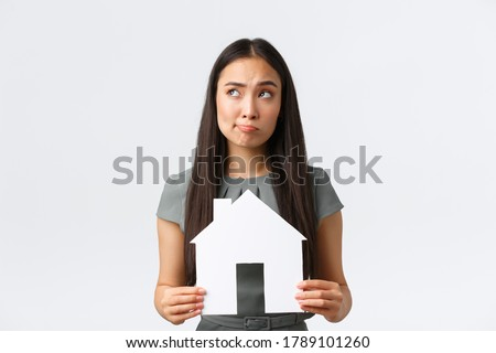 Insurance, loan, real estate and family concept. Indecisive and confused asian woman thinking about buying or renting home, holding paper house and looking away thoughtful, white background