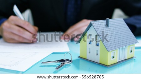 insurance of fire and theft .the hands of an insurer or real estate agent showing a house with floor plan and documents with ensured house keys.concept of home protection, family, insurance.rent house #556528705