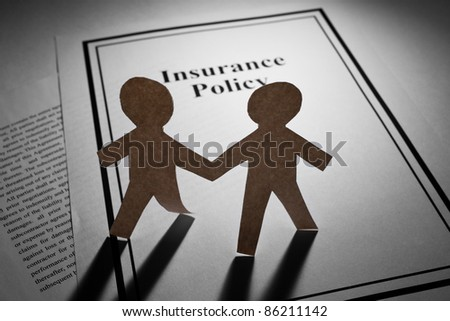 Insurance Policy and Paper Chain Men close up
